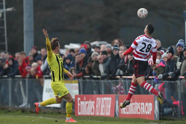 Kingstonian left-back Fabio Saraiva heads the ball at a sold-out King George's Field on Saturday. Pic: Simon Roe.