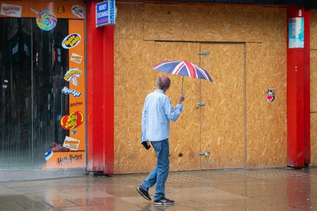 A man walks past a boarded-up shop