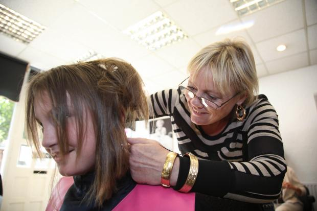 Shannon Dixon (10) having her hair cut by shop owner Julie Arnold