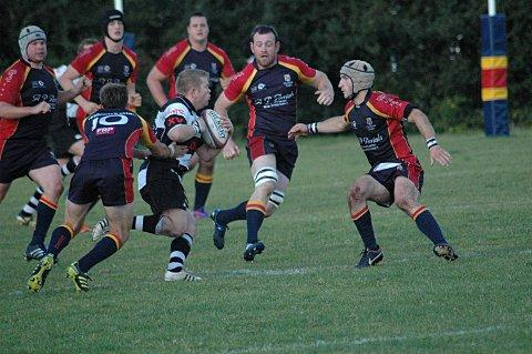 On the charge: Sutton & Epsom's Steve Warnham takes on the Chobham back line