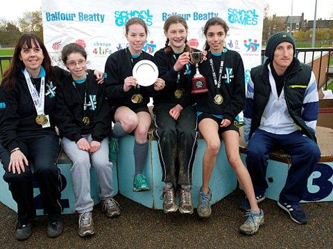 Medalists: The victorious girls' cross-country team with team manager Anne-Marie Osmonde (far left) and Scott Overall (far right)