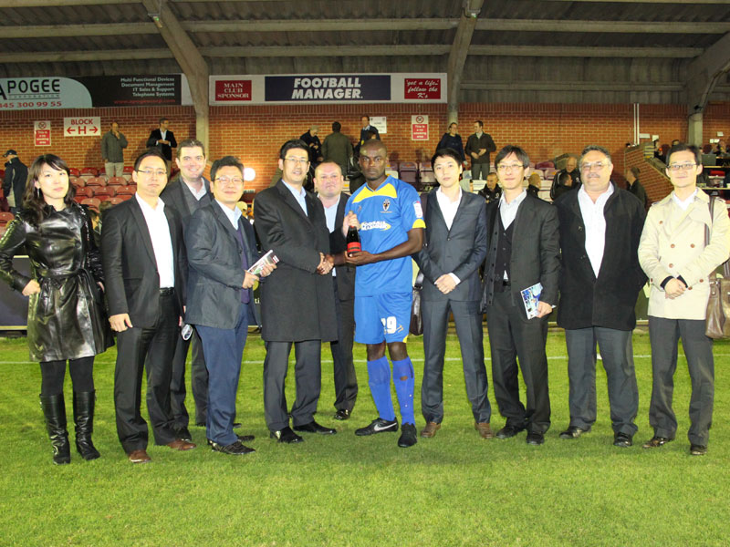 Nongshim representatives presenting the man of the match award before Wimbledon's home match against Torquay