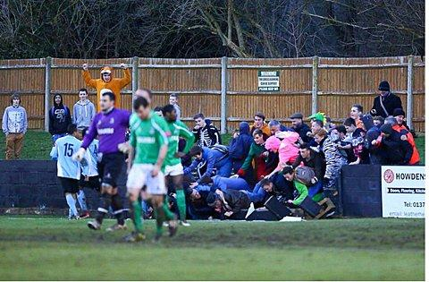 Scary moment: Celebrating fans are left sprawling after the wall collapsed when Dulwich Hamlet scored their second goal at Leatherhead – the match was abandoned with 12 minutes remaining			 Picture: Neil Hood