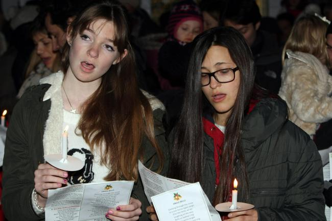 Dozens gather for carols by candlelight at stable yard service