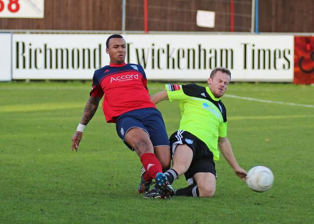 On his way: Hampton and Richmond Borough's Marcus Rose nips in to dispossess Met Police striker Allan Tait, right
