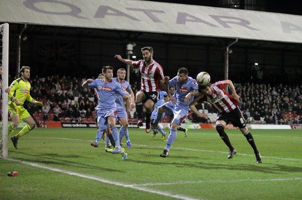 Up fot it: Brentford's Will Grigg, left, and midfielder Jonathan Douglas challenge at a corner on Tuesday night
