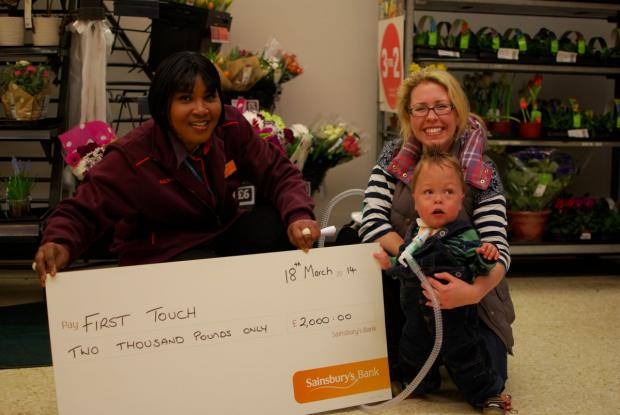 Baby Hugh Hunter with mum Louise Hunter receiving the cheque from Sainsbury's