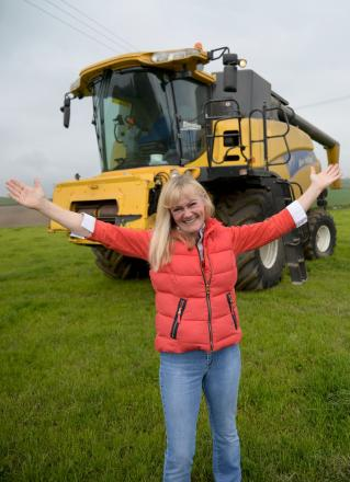 Judi James with a combine harvester. She will be driving a pink one today.