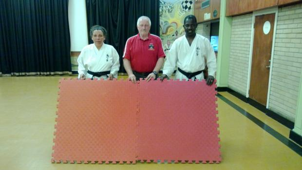 Diane Boyd, Mike Beasley and Jean Wedja with mats like the ones stolen