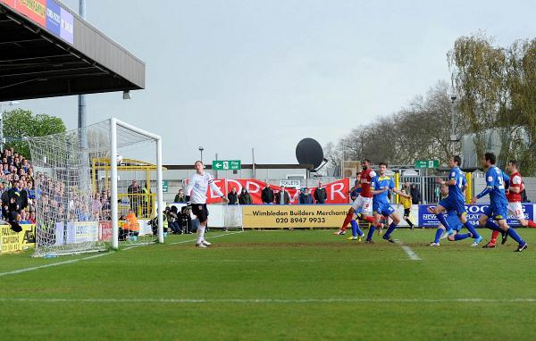 Header of a hero: Fleetwood Town keeper Tom Davies can only watch as Gary Alexander's header opens the scoring in the  eventual 2-1 win that kept AFC Wimbledon in League Two in 2012    					             SP73108