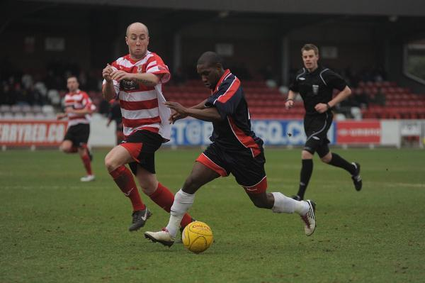 Switching teams: Ex-Carshalton Athletic winger Chris Henry, who is looking at a move to Kingstonian, bursts past former Ks midfielder Matt Gray  at Kingsmeadow in 2011