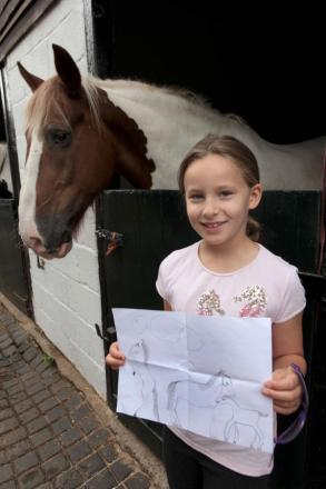 Amelia Hull, eight, with her picture of Joe the horse, behind.