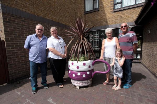 Mike Christie, residents, staff and Ava Burke (4) next to the striking plant pot.