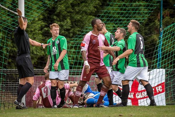 You and whose army?: Corinthian Casuals striker Carl Wilson-Dennis confronts a Burgess Hill Town defender after Casuals striker Jamie Byatt (9) collided with the Town goalkeeper on Saturday 	Picture: Stuart Tree