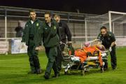 Carried off: Corinthian Casuals defender  Dan Bedford is wheeled off the King George's Field playing surface after breaking his leg