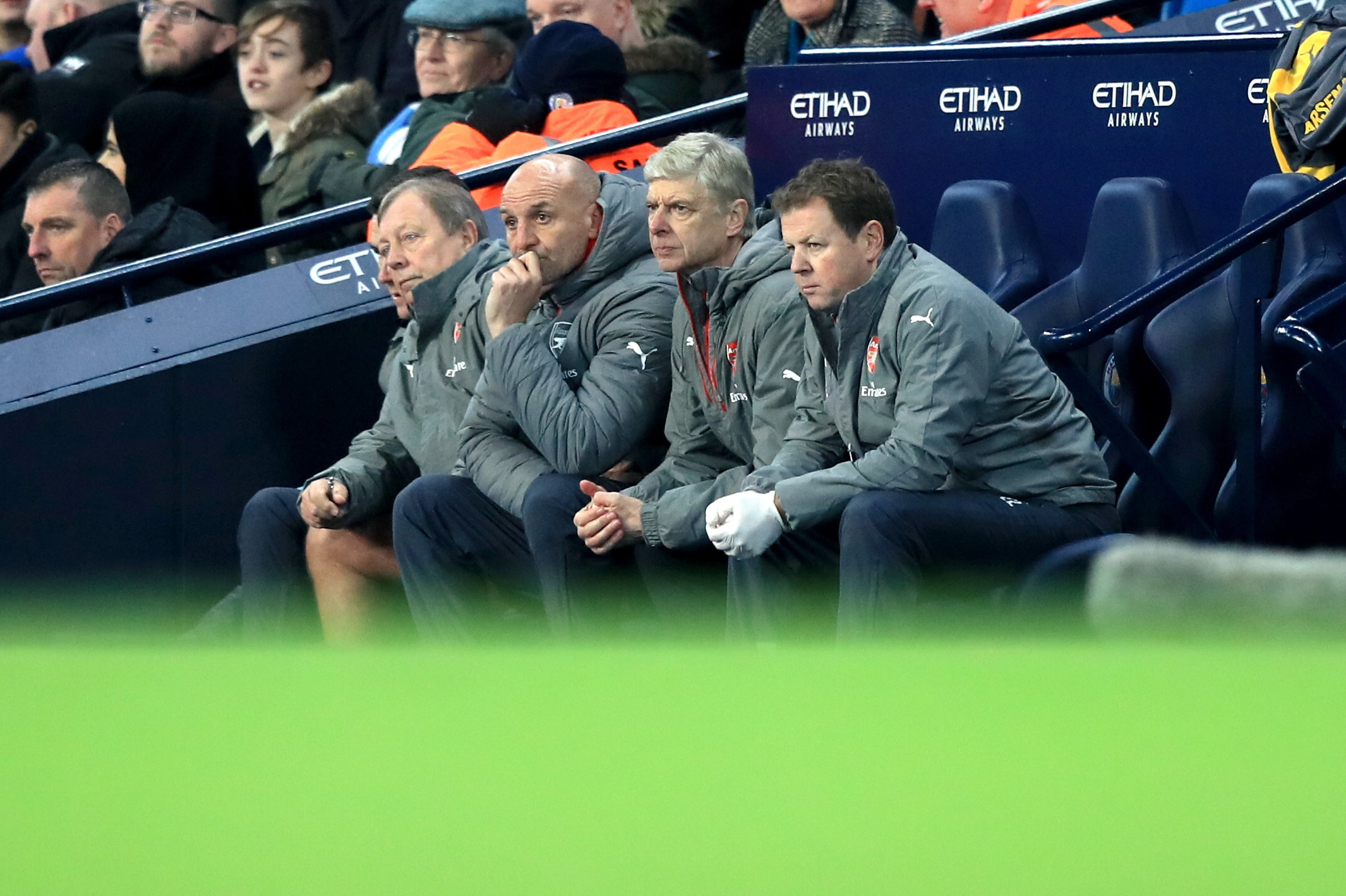 Arsenal manager Arsene Wenger sits on the bench with his coaching staff (Mike Egerton/Empics)