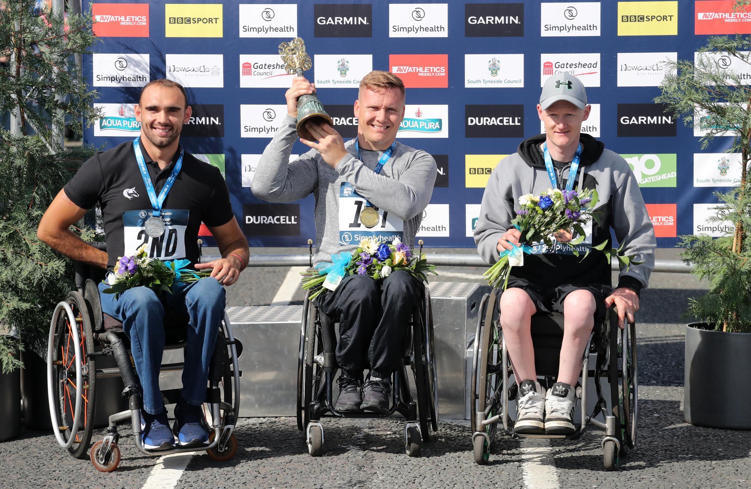 David Weir (centre) celebrates winning the Wheelchair Elite race during the 2018 Simply Health Great North Run. Photo: Richard Sellers / PA